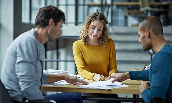Deux hommes et une femme travaillent sur une table